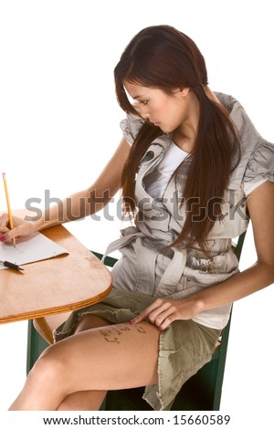 Young Asian female student stands by school desk and rights mathematical formulas on her thigh, so to be able to use cheat using it during math exam