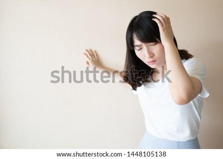 Young asian female suffering from dizziness, vertigo and headache over white background. Cause of dizzy inclued migraine, stress, stroke, BPPV, Meniere's disease or brain tumor. Health care problem.