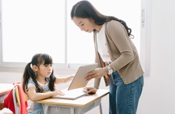 Young Asian female Teacher helping schoolgirl with digital tablet in computer Class. Education, elementary school, learning and technology concept.