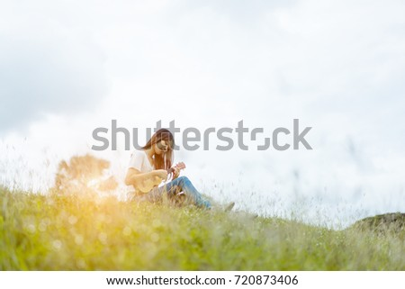 Young asian girl artist with ukulele classic, book and listening music singer pop solo sound smiling lifestyle in park nature summer of vacation time. #720873406