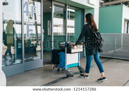 837efee095 young asian girl carrying luggage entering international airport. elegant  woman rolls light cart with luggage