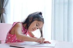 Young Asian girl cute kid using eraser on paper to erase what she had written. She is sitting on the chair working on table at home. Young creative kid activity concept.