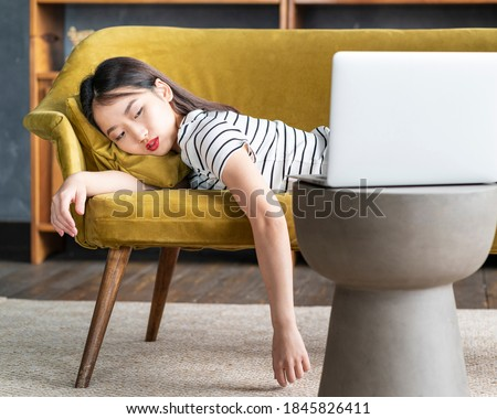 Young Asian girl fell asleep oncouch in front oflaptop. Cute bored woman watching boring movie, sad Sunday, dull leisure tired or overworked. Cozy home environment, soft sofa Stock photo ©