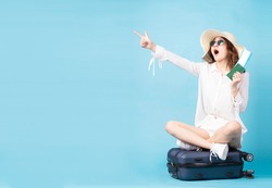 Young asian girl holding plane ticket and phone sitting on suitcase