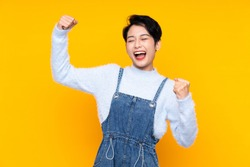 Young Asian girl in overalls over isolated yellow background celebrating a victory