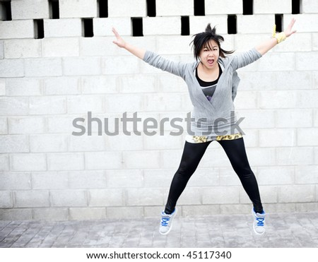 Young asian girl jumping in gym clothes