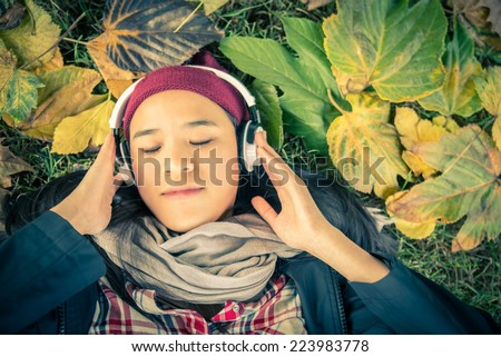 Young asian girl listening music in park. Student girl outside listening music with headphones and autumn leaves in the background