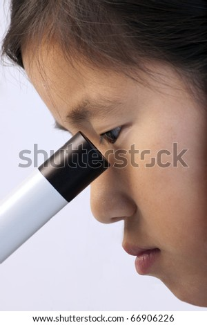 Young Asian girl looking into a microscope