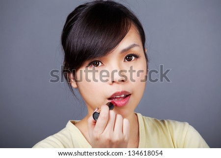 Young asian girl makes up her face