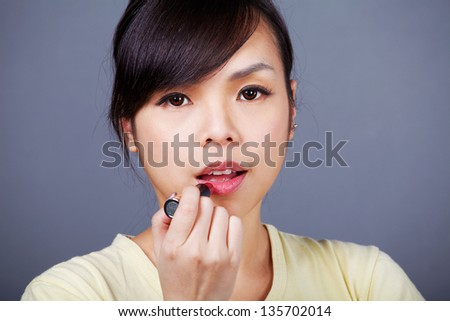 Young asian girl makes up her face - stock photo