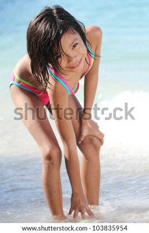 Young asian girl reaching for the sand in the beach.