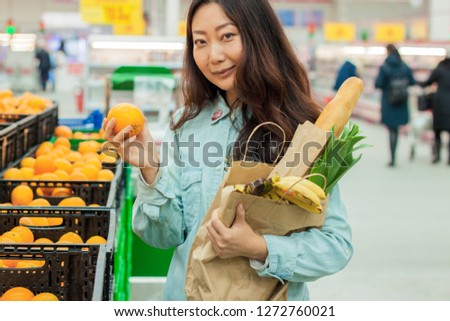 Young Asian girl shopping in a supermarket. Woman buys fruit and dairy product.