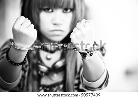 stock photo Young asian girl showing handcuffs on her wrists