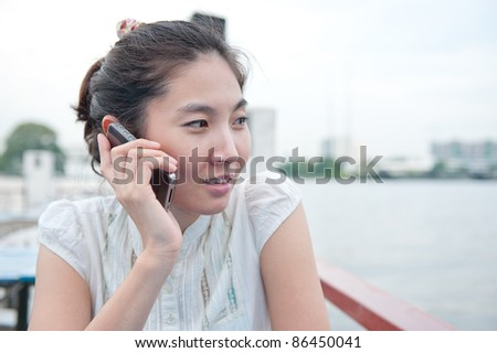 young asian girl talking telephone with riverside background(selective focus)
