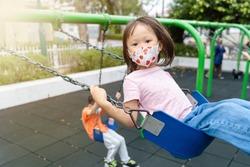 young asian girl wearing mask playing outdoor playground swinging having fun
