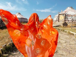 Young asian girl wearing traditional tribal cloth and scarves running in village with tents in the desert in Inner Mongolia. Fashion travel or trip concept photo red tribal scarf with gold decorations