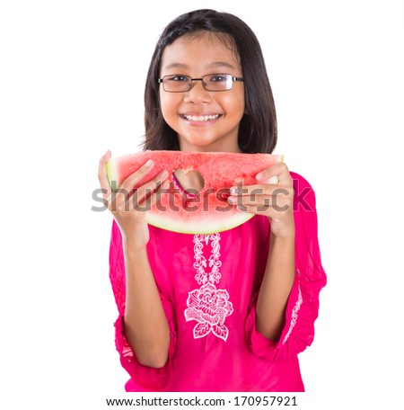 Young asian girl with a heart cut out out shape on a slice of watermelon over white background