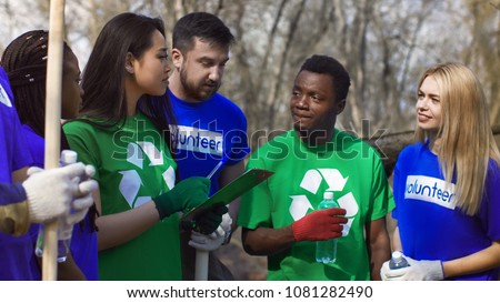 Young Asian girl with clipboard coordinating diverse volunteers for work of cleanup in spring forest.