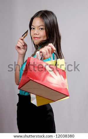 Young asian girl with shopping bags and credit card