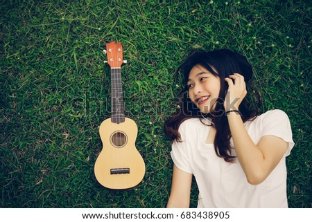 Young asian girl with ukulele and listening music smile lifestyle in park nature summer of vacation time,top view #683438905