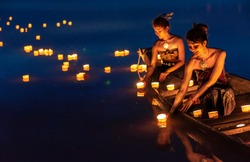 Young asian girls floating lanterns in the lake. The festival may originate from an ancient ritual praying respect to the water spirits.