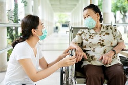 Young Asian grandchild taking care her grandmother sitting on wheelchair. Grandmother almost 90 years old was take care by her granddaughter while traveling at park. People wearing protective mask.