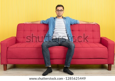 Young Asian handsome bearded man, wearing eyeglasses in denim shirt, sitting on center of red sofa, arms wide spread in confident, in modern living room, bright yellow stripe wall background