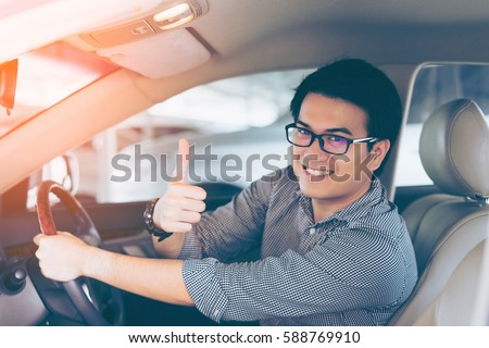 Young asian handsome man smiling and showing thumbs up in his car