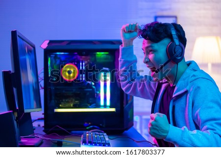 Young Asian Handsome Pro Gamer Feel Excited While playing in Online Cyber Sport Game at home