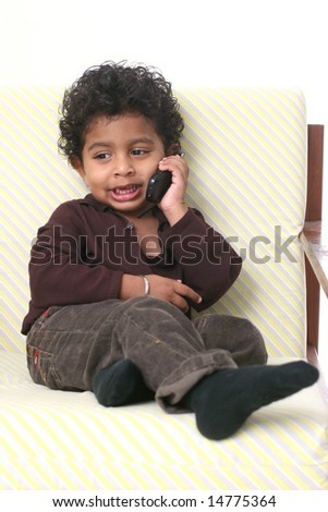 Young Asian Indian boy holding cell phone and smiling