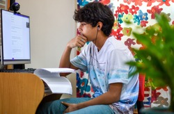 Young asian , Indian boy student virtual study at home. He using computer and learning online during COVID-19 pandemic.