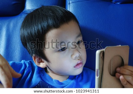 Young Asian kid staring at phone with blue background - Shutterstock ID 1023941311