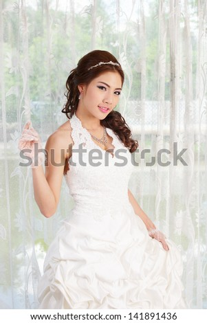 Young Asian lady in white bride dress, Model is Thai Ethnicity - stock photo