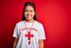 Young asian lifeguard girl wearing t-shirt with red cross using whistle over isolated background with a happy and cool smile on face. Lucky person.