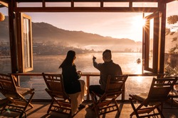 Young asian lover couple sitting on chair at a little cafe, Drinking coffee look at Sunrise in morning view mist and riverside view, Chinese settlement, Lee wine Rak Thai, Mae Hong Son, Thailand.