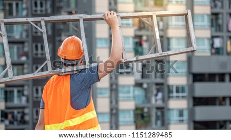 Young Asian maintenance worker man with orange safety helmet and vest carrying aluminium step ladder at construction site. Civil engineering, Architecture builder and building service concepts #1151289485
