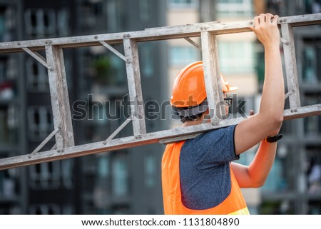Young Asian maintenance worker with orange safety helmet and vest carrying aluminium step ladder at construction site. Civil engineering, Architecture builder and building service concepts #1131804890