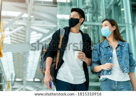 young Asian male and female couple tourists drag luggages walking through the hallway after arrival ,two asian people traveller wearing facial face mask virus protection safety travel ideas concept