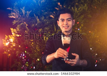 Young Asian male bartender mixing alcohol drink cocktail in glass wine at outdoors night club. People lifestyles and occupation. Job and occupation concept. Christmas and New year event festival theme