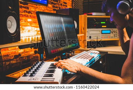young asian male composer playing midi keyboard for arranging a song on computer in home studio