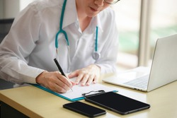 Young Asian male doctor is recording a medical history on the clipboard and explaining something to the female patient. Medical and health care concepts