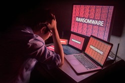 Young Asian male frustrated, confused and headache by ransomware attack on desktop screen, notebook and smartphone, cyber attack and internet security concepts
