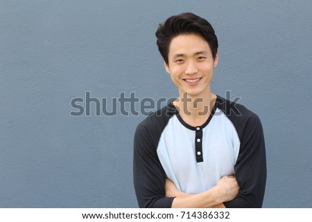 Young Asian male smiling and laughing with arms crossed