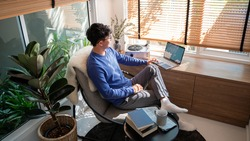 Young asian male tech user relaxing  holding laptop computer and looking at the screen in living room, Remote Job or work from home concept