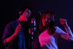 Young Asian man and woman singing to condenser microphone in studio. Professional vocalist wearing headphone while performing in voice recording room. Couple duet song and music production concept.
