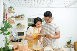 Young asian man and woman together cooking cake and bread with egg, looking menu from tablet in the flour happy relaxing in at home