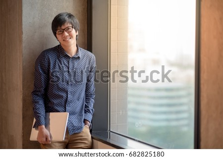 Young Asian man dressed in casual style holding laptop computer. high school or university college student, educational concept #682825180