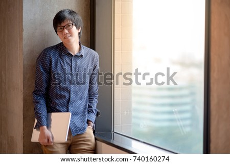 Young Asian man dressed in casual style holding laptop computer. high school or university college student, educational concept #740160274