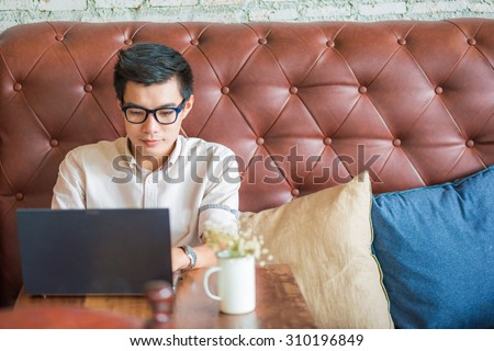Young asian man drinking coffee in cafe and using laptop computer, Art coffe shop