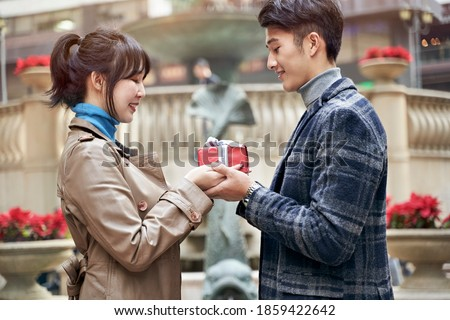 young asian man giving girlfriend a christmas or birthday gift